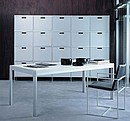 Piece of funiture upon wheels equipped with doors and file holder. Strucutre, shelves and front parts in aluminium. In the foreground Lounge table in white laminate.