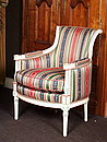 Directoire period style easy chair with a curved back which sides are arm-rests and which supports are in extension with feet, lacquer ivory on skin glue with rims gilded with copper leaves,...