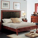 Bed in solid cherry wood with upholstered headboard.
